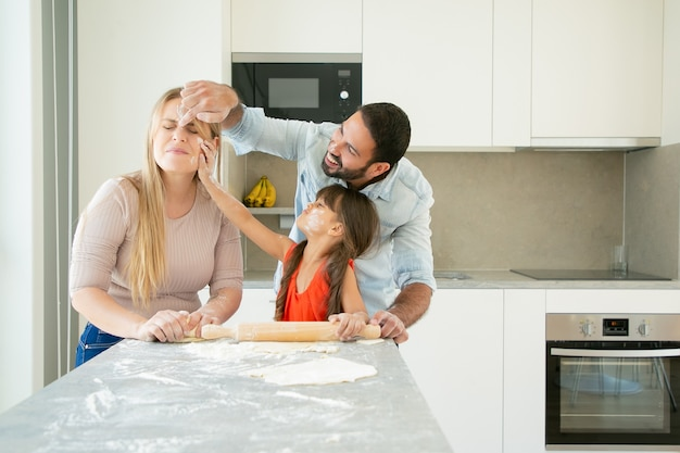 Feliz mãe positiva, pai e filha manchando rostos com pó de flor enquanto assam juntos Foto gratuita