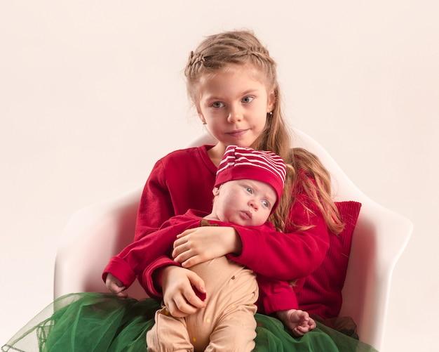 Feliz menina adolescente segurando sua irmãzinha bebê recém-nascido. amor de familia. Foto gratuita