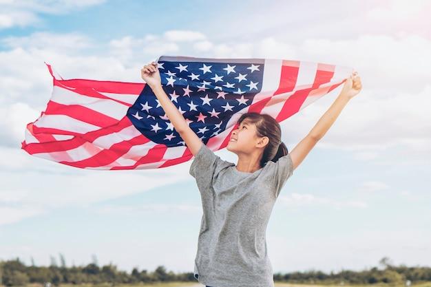 Feliz menina asiática com bandeira americana eua comemorar 4 de julho Foto Premium
