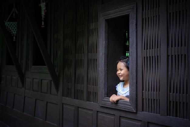 Feliz menina asiática em pé junto à janela Foto Premium