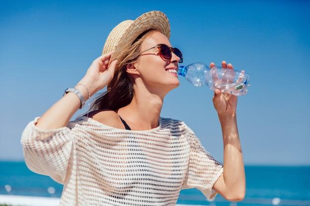Feliz menina bonita em óculos de sol bebendo água limpa, durante a caminhada no cais Foto gratuita