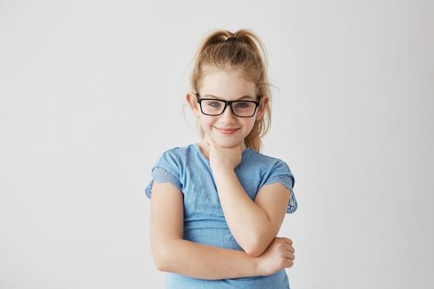 Feliz menina loira pequena de olhos azuis com expressão feliz e pacífica em novos óculos escuros. Foto gratuita