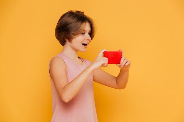 Feliz menina moderna usando smartphone para gravação de vídeo isolado Foto gratuita