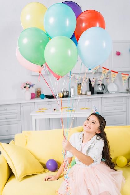 Feliz, menina, sentar sofá, segurando, balões coloridos Foto gratuita