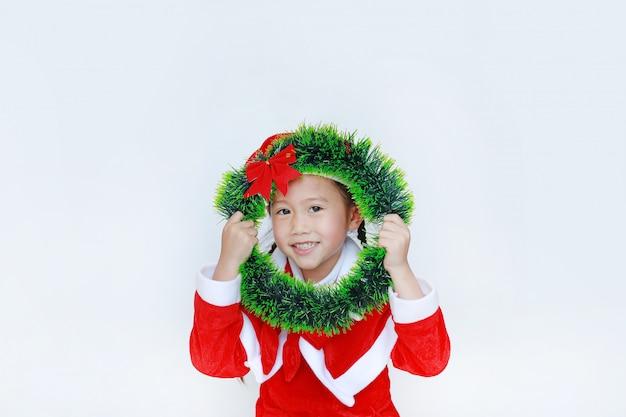 Feliz, menininha, em, traje santa, segurando, natal, redondo, grinalda, ligado, dela, rosto, branco, bac Foto Premium
