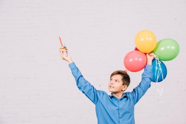 Feliz, menino adolescente, segurando, muffin, e, balões coloridos, levantamento, seu, mão Foto gratuita