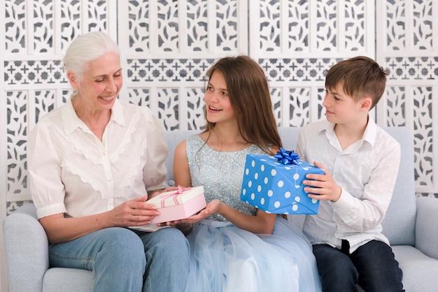 Feliz, menino menina, dar, caixas presente, para, seu, vó, em, partido aniversário Foto gratuita