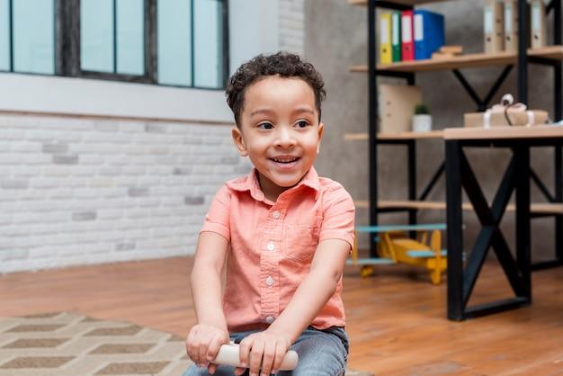 Feliz, menino preto, dirigindo, carro brinquedo Foto gratuita