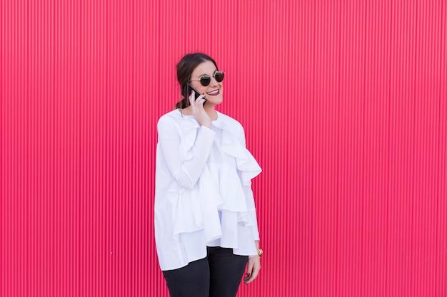 Feliz moda linda jovem tendo uma conversa usando um smartphone e sorrindo. vermelho. Foto Premium