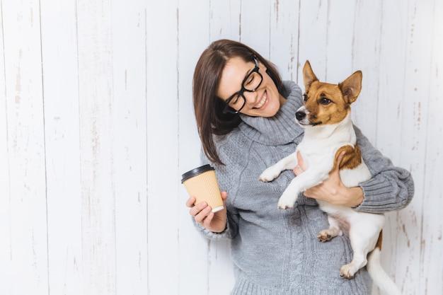 Feliz modelo feminino morena usa camisola de malha quente, óculos, carrega seu cão favorito e café para viagem Foto Premium