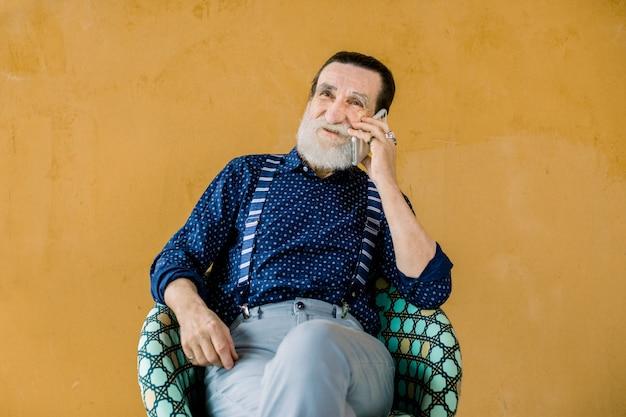 Feliz moderno na moda homem barbudo cinza na elegante camisa azul escura, suspensórios e calças cinza, sentado na cadeira em fundo amarelo e falando de telefone Foto Premium