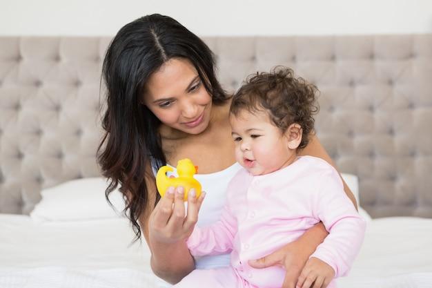 Feliz morena mostrando pato amarelo para seu bebê no quarto Foto Premium