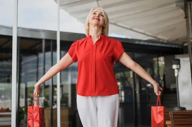 Feliz mulher adulta segurando sacolas de compras Foto gratuita