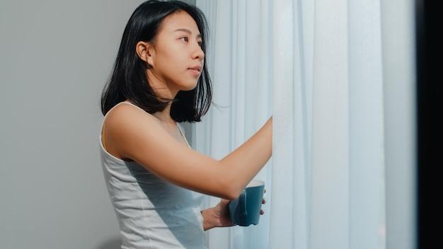 Feliz mulher asiática linda sorrindo e bebendo uma xícara de café ou chá perto da janela no quarto. jovem latina abrir cortinas e relaxar de manhã. senhora de estilo de vida em casa. Foto gratuita