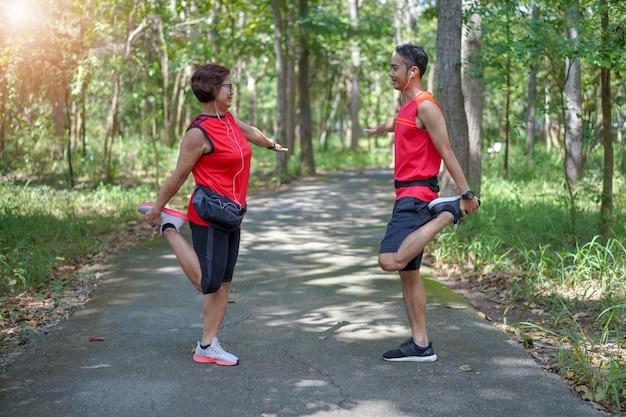 Feliz mulher asiática sênior com homem ou personal trainer esticar os músculos da coxa no parque Foto Premium