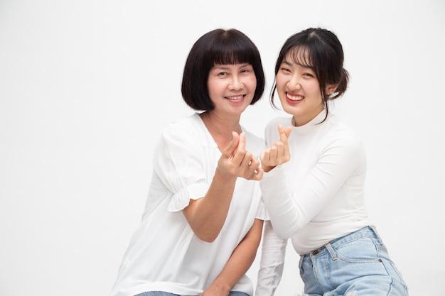 Feliz mulher asiática sênior e filha com mini coração assinar juntos isolado Foto Premium
