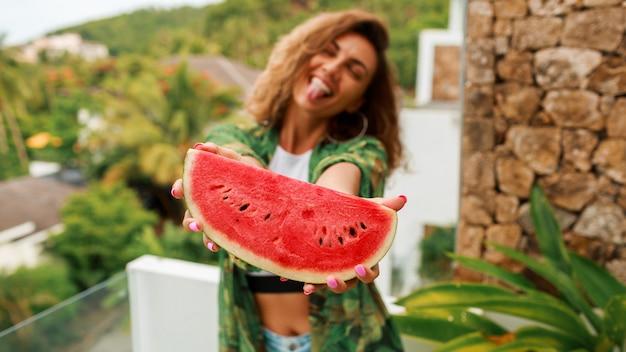 Feliz mulher bonita com cabelos ondulados, segurando a melancia. Foto gratuita