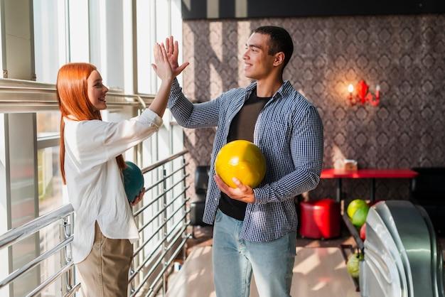 Feliz mulher e homem segurando bolas de boliche coloridas Foto gratuita