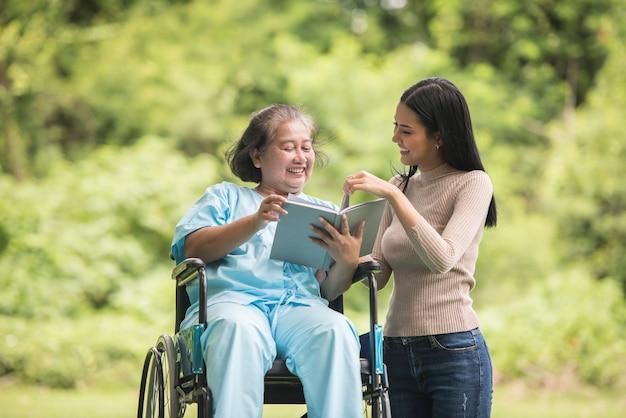 Feliz, mulher, em, um, cadeira rodas, lendo um livro, com, dela, filha, parque Foto gratuita