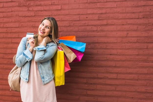 Feliz, mulher, ficar, com, bolsas para compras, e, cartão crédito, em, parede tijolo Foto gratuita