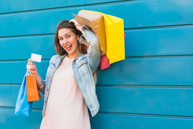 Feliz, mulher, ficar, com, bolsas para compras, e, cartão crédito Foto gratuita