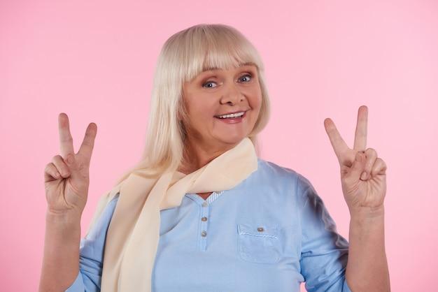 Feliz mulher idosa mostra sinal de vitória. sinal de paz. Foto Premium