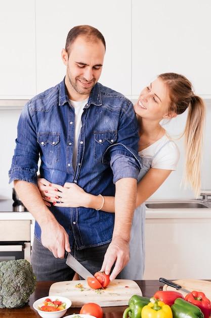 Feliz, mulher jovem, amando, dela, marido, legumes cortantes, com, faca, em, cozinha Foto gratuita