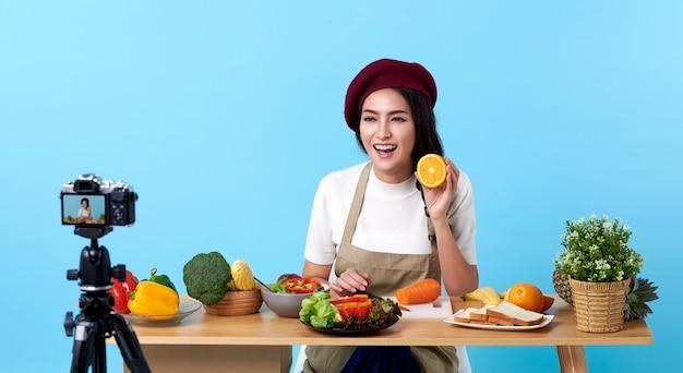 Feliz mulher jovem asiática na moda estilo olhar e gravar vídeo com câmera cozinhar alimentos Foto Premium