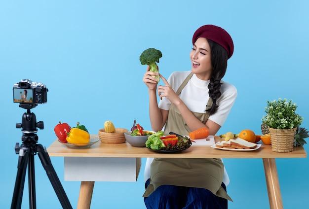 Feliz mulher jovem asiática no estilo de olhar de moda e filmar vídeo com câmera, cozinhar alimentos saudáveis é blogueira apresentando para pessoas sociais. ela é influenciadora nas redes sociais online. Foto Premium