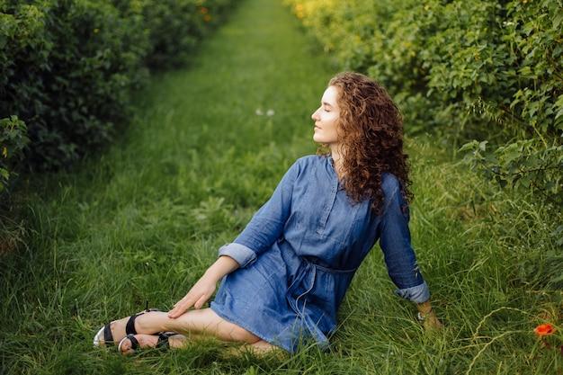 Feliz mulher jovem com cabelos cacheados castanhos, vestido, posando ao ar livre em um jardim Foto gratuita