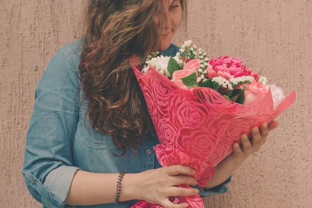 Feliz, mulher jovem, em, brim, vestido, com, buquê, de, gentil, fresco, flores Foto Premium