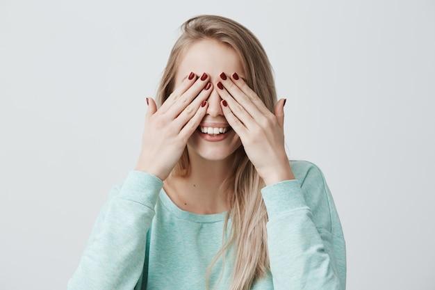 Feliz mulher jovem feliz com cabelos loiros, fecha os olhos com as mãos Foto gratuita