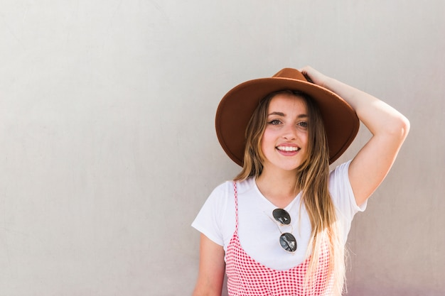 Feliz, mulher jovem, posar, com, chapéu Foto gratuita