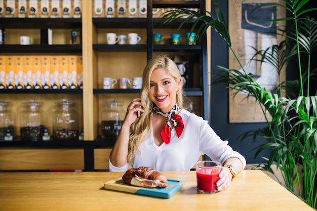 Feliz, mulher jovem, segurando, telefone móvel, em, mão sentando, escrivaninha, com, pão assado, e, suco Foto gratuita