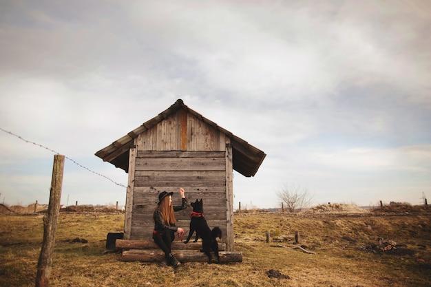 Feliz, mulher jovem, sentando, com, dela, cachorro preto Foto Premium