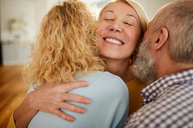 Feliz mulher madura, abraçando amigos | Foto Premium