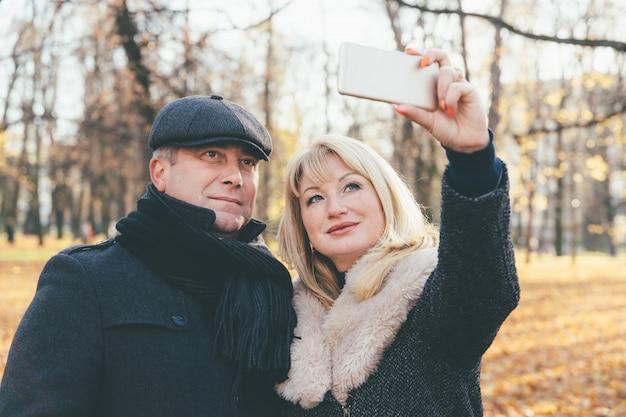Feliz mulher madura loira e bela morena de meia-idade tomar selfie no celular. Foto Premium