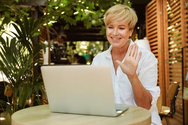Feliz mulher madura, sentado em um café com laptop Foto Premium