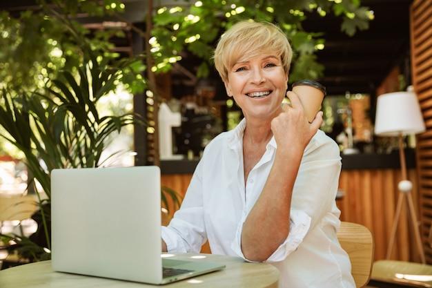 Feliz mulher madura, sentado em um café com o computador portátil Foto Premium
