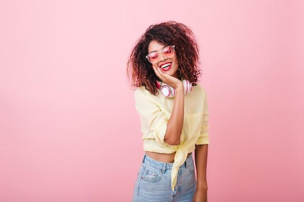 Feliz mulher magro de cabelos castanhos em uma camisa elegante, sorrindo com um interior bonito. jovem muito mulata de óculos elegantes, rindo enquanto posava com roupa nova. Foto gratuita