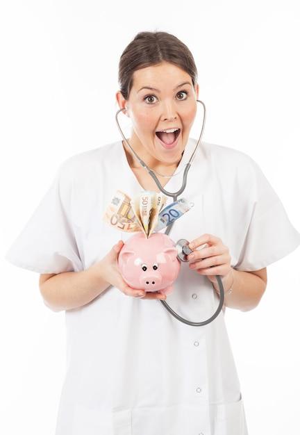 Feliz mulher médico com cofrinho cheio de dinheiro Foto Premium