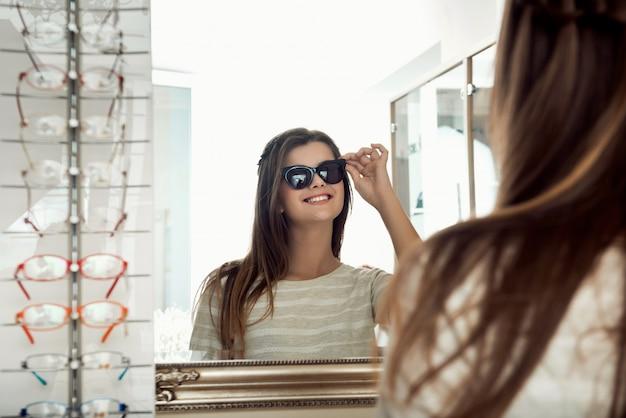 Feliz mulher morena atraente olhando no espelho enquanto experimentava óculos de sol na loja de óptica Foto gratuita