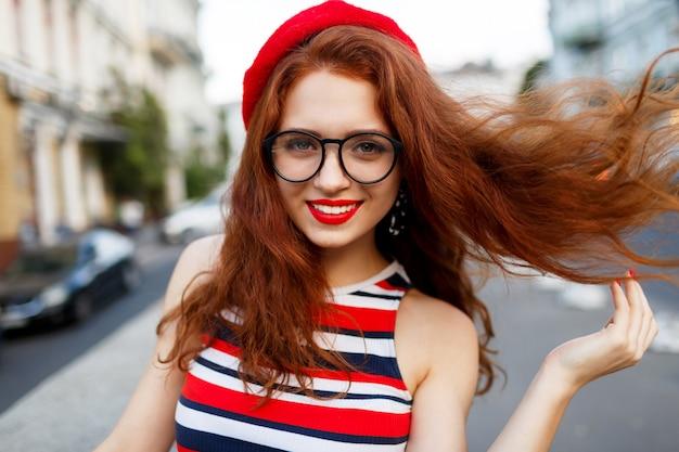 Feliz mulher ruiva fabulosa elegante boina vermelha na rua Foto gratuita