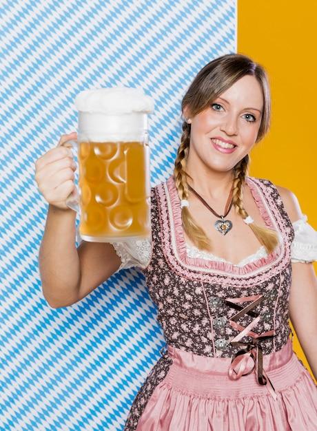 Feliz mulher segurando a caneca de cerveja Foto gratuita