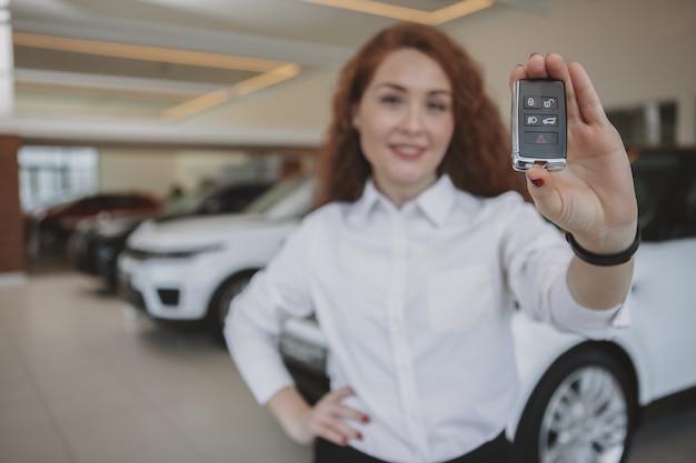 Feliz mulher segurando as chaves do carro para seu novo automóvel Foto Premium
