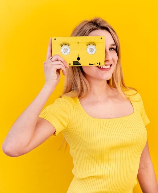 Feliz mulher segurando cassete antiga Foto gratuita
