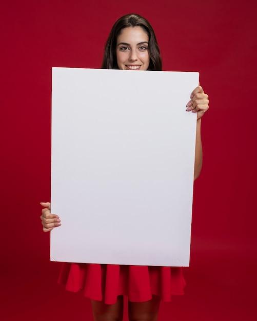 Feliz mulher segurando uma faixa vazia Foto gratuita