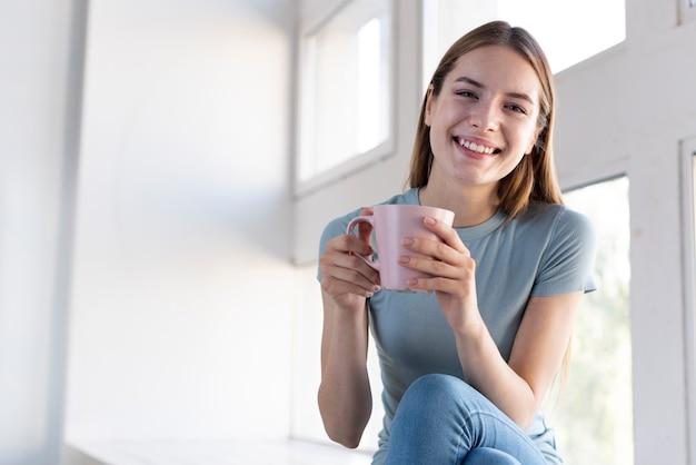 Feliz mulher segurando uma xícara de café Foto gratuita