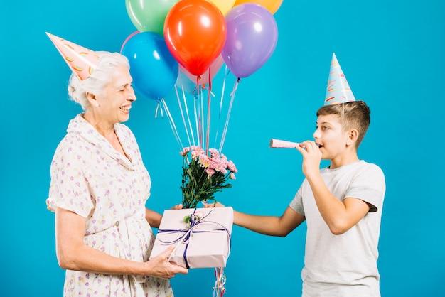 Feliz, mulher sênior, com, presente aniversário, e, flores, olhar, dela, neto, soprando, partido, chifre Foto gratuita