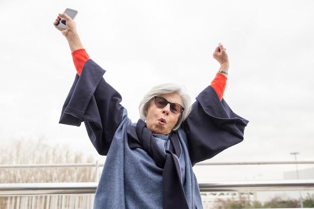 Feliz mulher sênior, levantando os braços e gritando ao ar livre Foto gratuita
